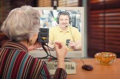 Grå haired kvinna som lär datorkringutrustningar Arkivfoto