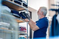 Grå haired man som uttrycker munterhet i shoppinglager arkivfoton