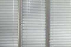 Grå horisontaljalousie i fönster Arkivfoton