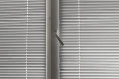 Grå horisontaljalousie i fönster Arkivbilder