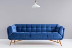 Grå inre med den stilfulla stoppade soffan Royaltyfri Bild