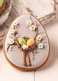 Grå kaka för påsk med dekorativa easter ägg och blommor nära vita skärbrädor arkivbilder