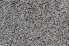 Grå konkret backgroundl med små stenar arkivbilder