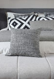 Grå kudde på bänk med entonig sängkläder Royaltyfri Bild