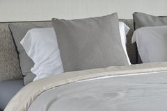 Grå kudde på den vita inställningen på säng med den väl till mods filten fotografering för bildbyråer