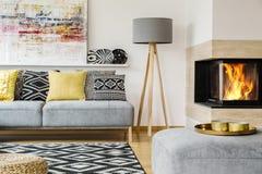 Grå lampa mellan spisen och soffan med mönstrade kuddar in Arkivbild