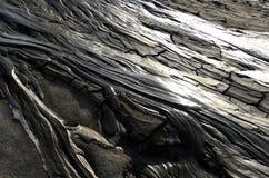 Grå lava från gyttjavulkan Arkivfoto