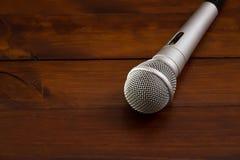 Grå mikrofon på en stilfull mörk träbakgrund Arkivfoto