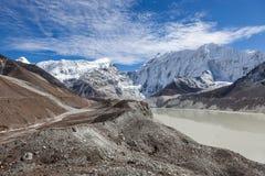 Grå moränsjö och snöig bergmaximum in Royaltyfri Foto