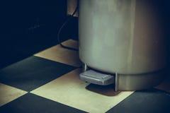 Grå plast- soptunna med pedalen på grön golvmodell Arkivbilder
