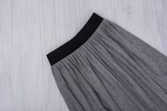 Grå plisserad kjol på träbakgrund trendigt begrepp Cl arkivfoto