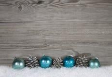 Grå sjaskig chic julbakgrund med trä, grankotten och lodisar Royaltyfri Bild