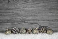 Grå sjaskig chic julbakgrund med trä, grankotten och lodisar Royaltyfria Foton