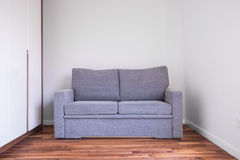 Grå soffa i tomt rum arkivfoton