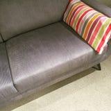 Grå soffa med den färgrika randiga kudden royaltyfri fotografi