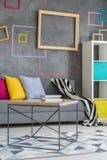 Grå soffa med färgrika kuddar arkivbilder