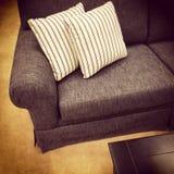 Grå soffa med randiga vita kuddar Royaltyfria Bilder