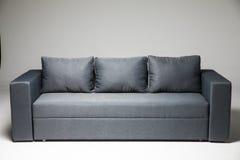 Grå soffa som isoleras på grå bakgrund arkivfoto