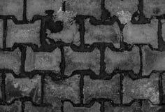 Grå tegelsten avmaskar på vägen Arkivbilder