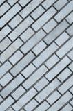 Grå tegelstenvägg för bakgrund och textur Arkivfoto