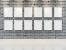 GRÅ TEGELSTENVÄGG med ramar för målningar Arkivbilder