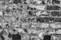 Grå textur av en gammal vägg av en forntida byggnad med ett förstört murbruklager och spruckna tegelstenar Arkivbild
