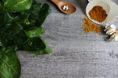 Grå trätabell med grönsaker, lökar, champinjoner, peppar, a Arkivfoto