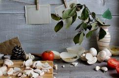Grå trätabell med grönsaker, lökar, champinjoner, peppar, a Fotografering för Bildbyråer