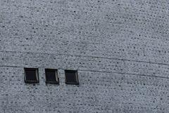 Grå vägg med cementtextur och tre svarta fyrkantiga fönster royaltyfria bilder