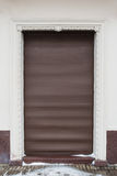 Grå vägg med den bruna metalldörren Royaltyfri Foto