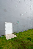 Grå vägg med den vita dörren fotografering för bildbyråer