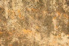 Grå vit gul gammal slagen betongvägg med orange fläckar, djupa skrapor och fläckar av mossa och formen Textur för grov yttersida royaltyfria bilder
