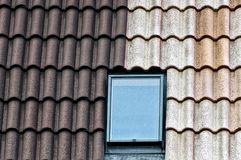 Gråa brunttegelplattor och ett glass fönster på taket av byggnaden Arkivbild