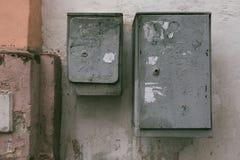 Gråa elektriska askar på bakgrunden av en gammal mång--färgad vägg royaltyfri bild