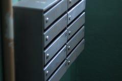 Gråa färgmetallpostboxes på en bakgrundsvägg för grön färg Arkivbild