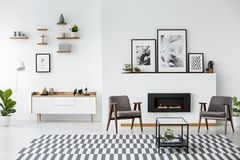 Gråa fåtöljer mellan den svarta spisen i den rymliga lägenheten int arkivbilder