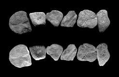 Gråa granitstenar på svart Arkivfoton