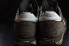 gråa gymnastikskor som lämnas i mjuka krusiga sander på stranden royaltyfria bilder