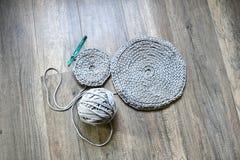 Gråa handgjorda cottoncordborddukar på virkningkroken Royaltyfri Bild