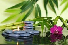 Gråa kiselstenar som är ordnade i Zenlivsstil med bambustjälk, en orkidé och en tänd stearinljus royaltyfria foton