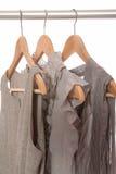 Gråa klänningar är på hängare. royaltyfri foto