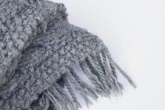 Gråa scarves på vita bakgrunder royaltyfria bilder