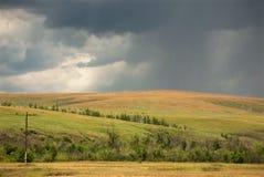 Gråa stormiga himmel- och regnlinjer över gula fält royaltyfri foto