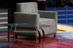 Gråa väntande på gäster för stol- och exponeringsglastabell grå stol i kontoret eller studion för besökare och förhandlingar affä arkivbild