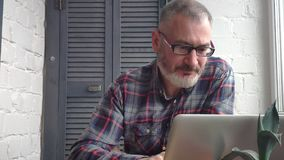 Gråhårig skäggig manlig revisor som hemma arbetar bak en bärbar dator som gör en rapport mot bakgrunden av en minimalist inre arkivfilmer