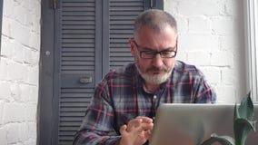 Gråhårig skäggig manlig revisor som hemma arbetar bak en bärbar dator som gör en rapport mot bakgrunden av en minimalist inre lager videofilmer
