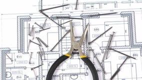 Gråna och gulna runda-näsan plattång på byggnadsplan lager videofilmer