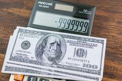 Gråta den Franklin dollarräkningen på calulator arkivfoton