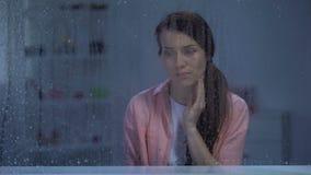 Gråta den medelåldersa kvinnan som ser till och med regnigt fönster, liv och hälsoproblem arkivfilmer