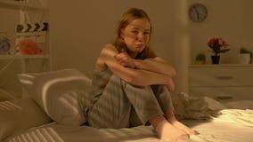 Gråta ensamt kvinnligt sammanträde på säng som ser kameran, problemhopplöshet, ånger arkivfilmer